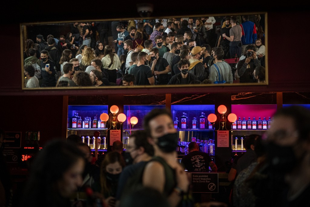 People talk and drink before a concert in Barcelona, Spain, Saturday, Dec. 12, 2020. Eager for a live music show after months of social distancing, mo...