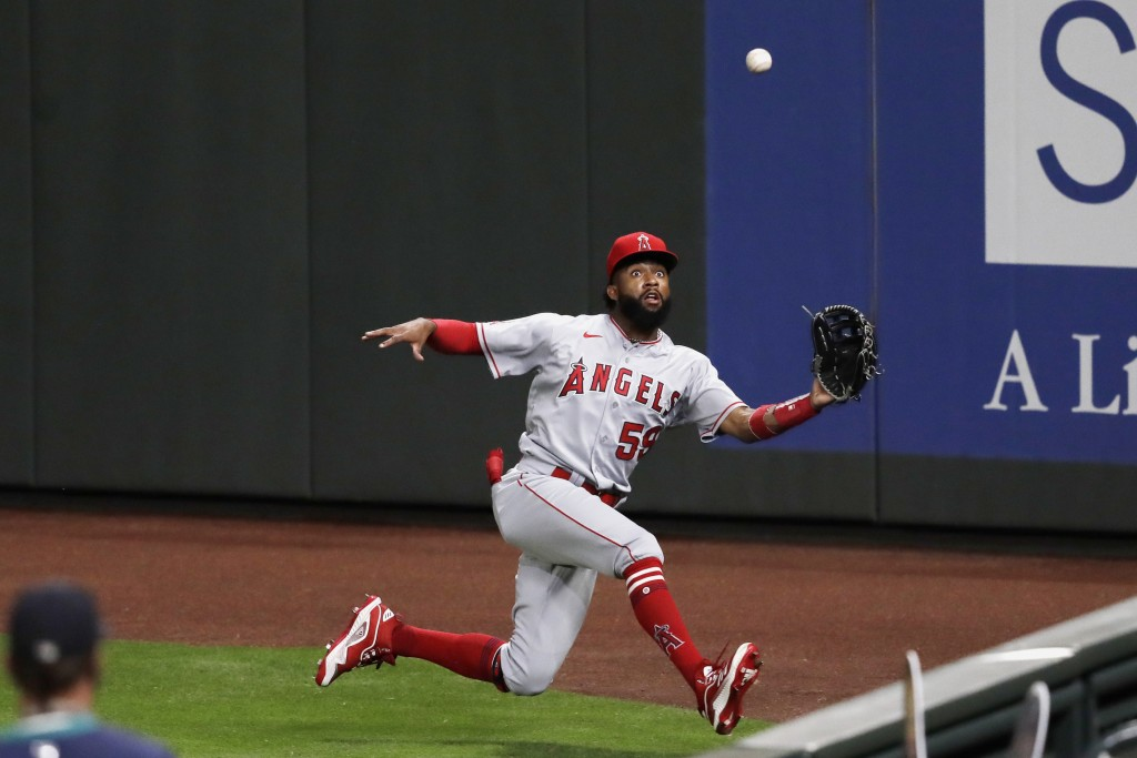 FILE - In this Aug. 5, 2020, file photo, Los Angeles Angels right fielder Jo Adell tries to catch a deep fly ball from Seattle Mariners' Evan White du...