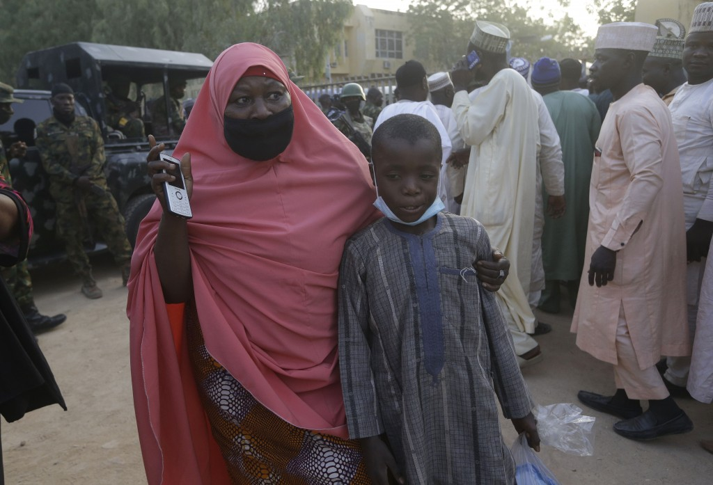 A mother is reunited with her freed schoolboy son who was among the kidnapped students in Katsina, Nigeria Friday, Dec. 18, 2020. More than 300 school...