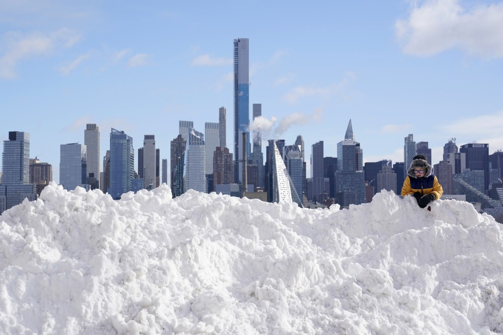 A boy plays on a mound of snow in front of the skyline of New York City in West New York, N.J., Thursday, Dec. 17, 2020. The first major snowstorm of ...