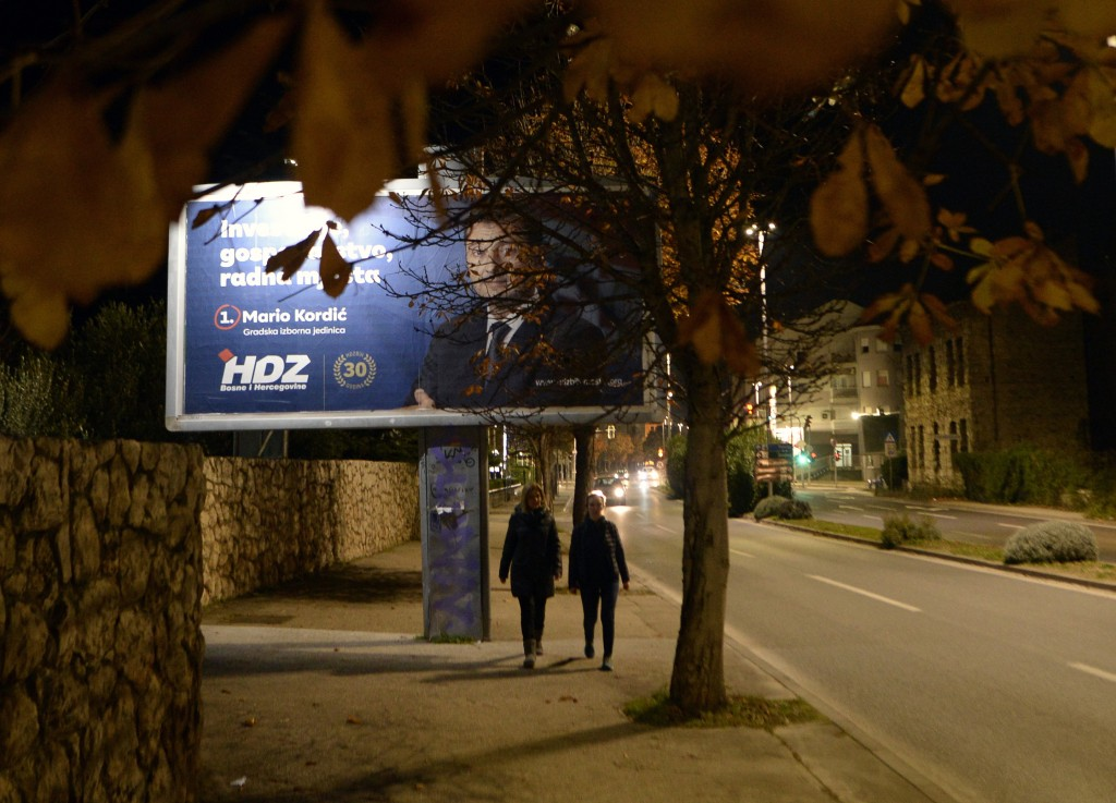 Two women pass by pre-elections billboards in Mostar, Bosnia, Friday, Dec. 18, 2020. Bosnia's ethnically divided southern city of Mostar is holding it...