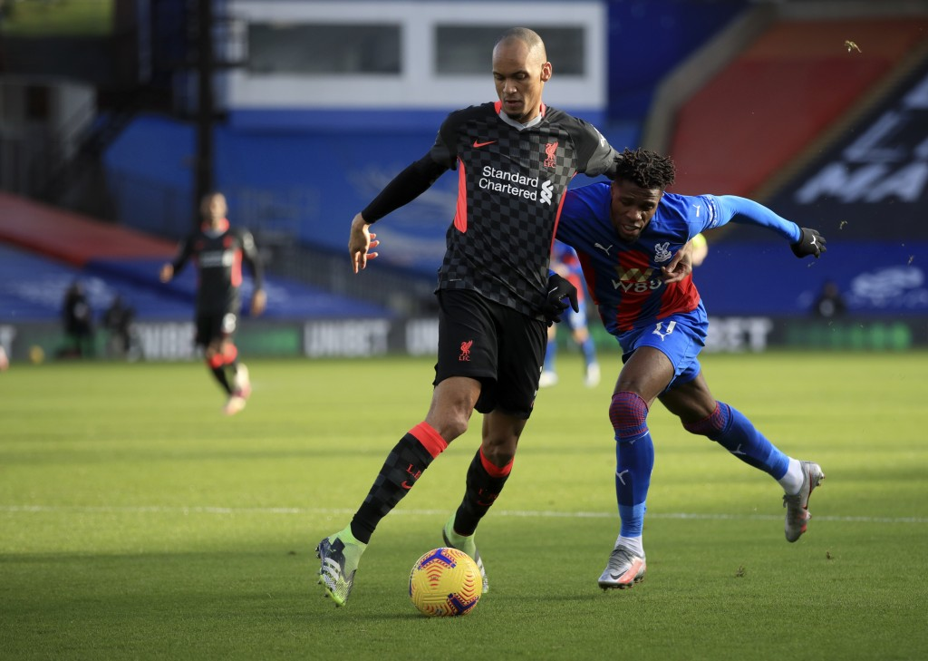 Liverpool's Fabinho, left, duels for the ball with Crystal Palace's Wilfried Zaha during the English Premier League soccer match between Crystal Palac...