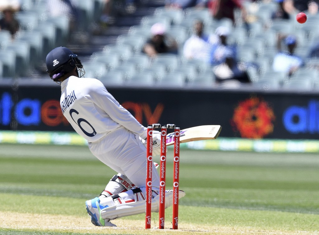 India's Wriddhiman Saha swerves to avoid a high delivery from Australia on the third day of their cricket test match at the Adelaide Oval in Adelaide,...