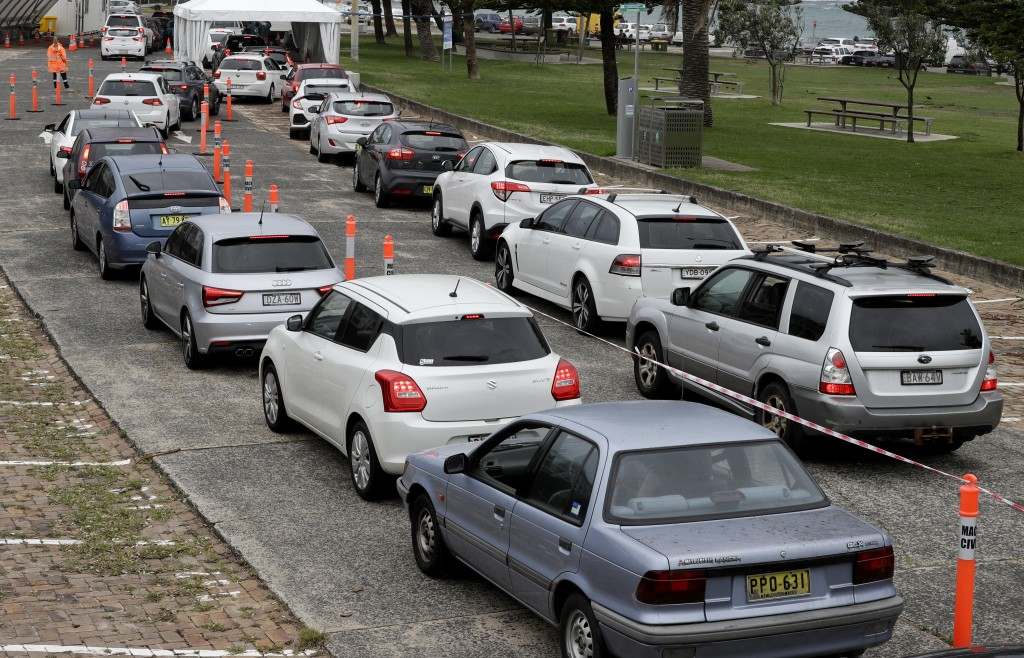 People queue at a drive through COVID-19 testing station at a beach in Sydney, Australia, Saturday, Dec. 19, 2020. Sydney's northern beaches will ente...