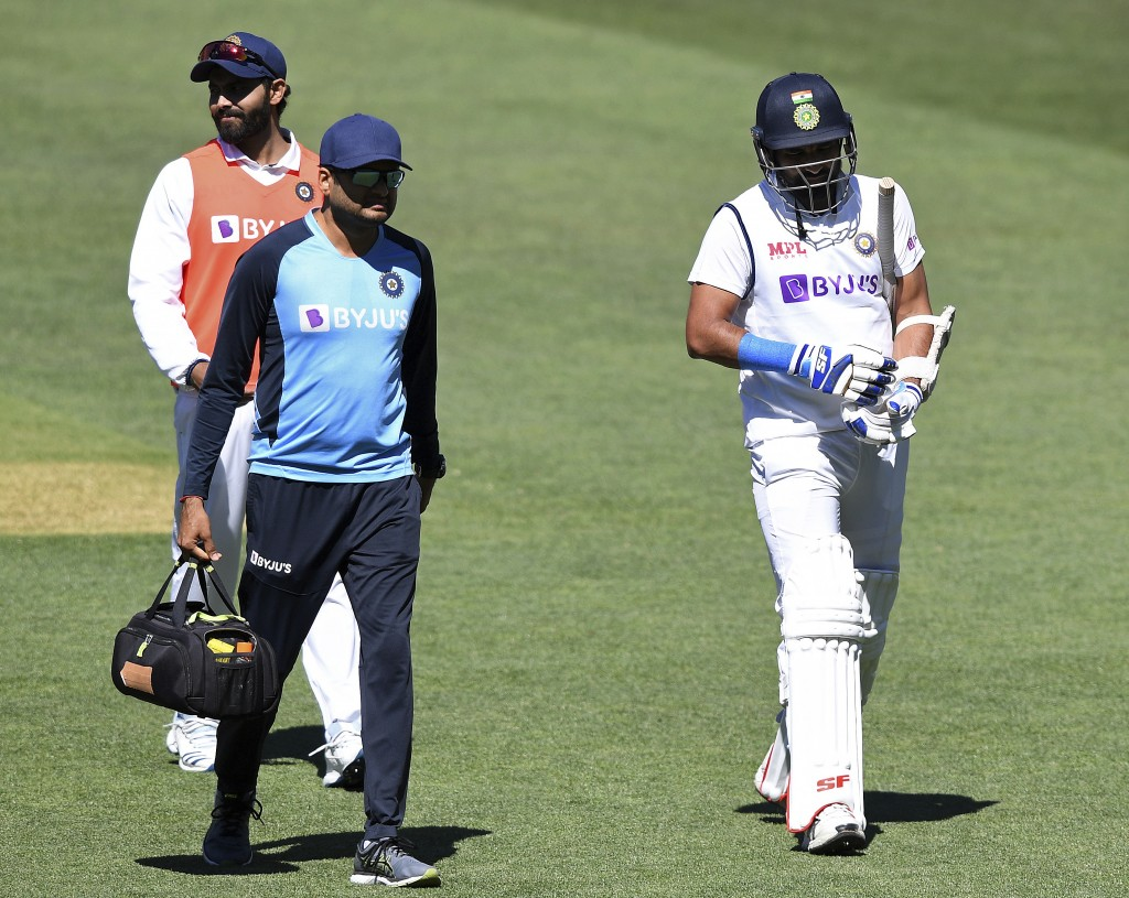 India's Mohammed Shami, right, retires hurt after he was struck on the forearm on the third day of their cricket test match against Australia at the A...