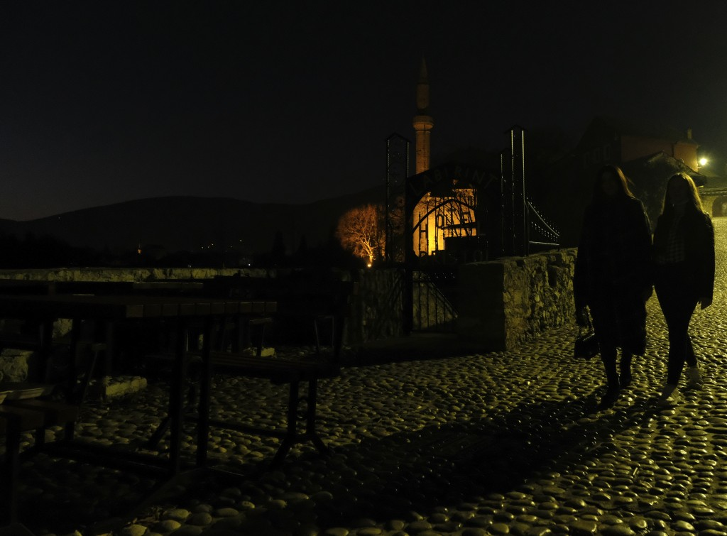 Two women walk in the center of Old City of Mostar, Bosnia, Friday, Dec. 18, 2020. Bosnia's ethnically divided southern city of Mostar is holding its ...