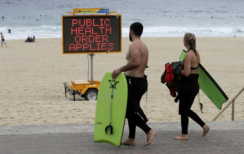 A sign warns people at a beach in Sydney, Australia, Saturday, Dec. 19, 2020. Sydney's northern beaches will enter a lockdown similar to the one impos...