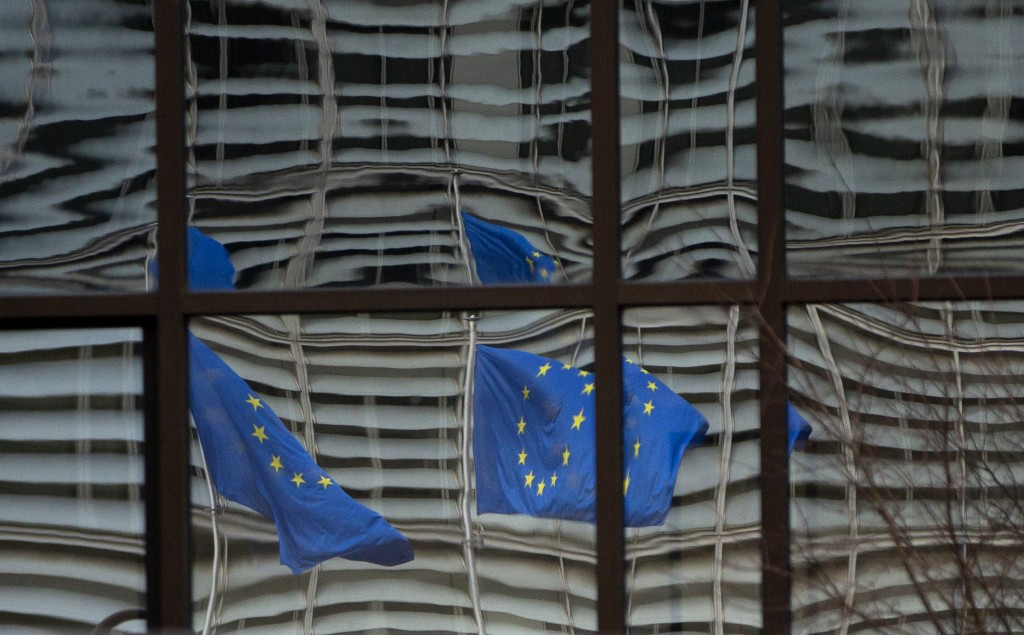 European Union flags are reflected in a window of the European Council in Brussels, Saturday, Dec. 19, 2020. The European Union and the United Kingdom...