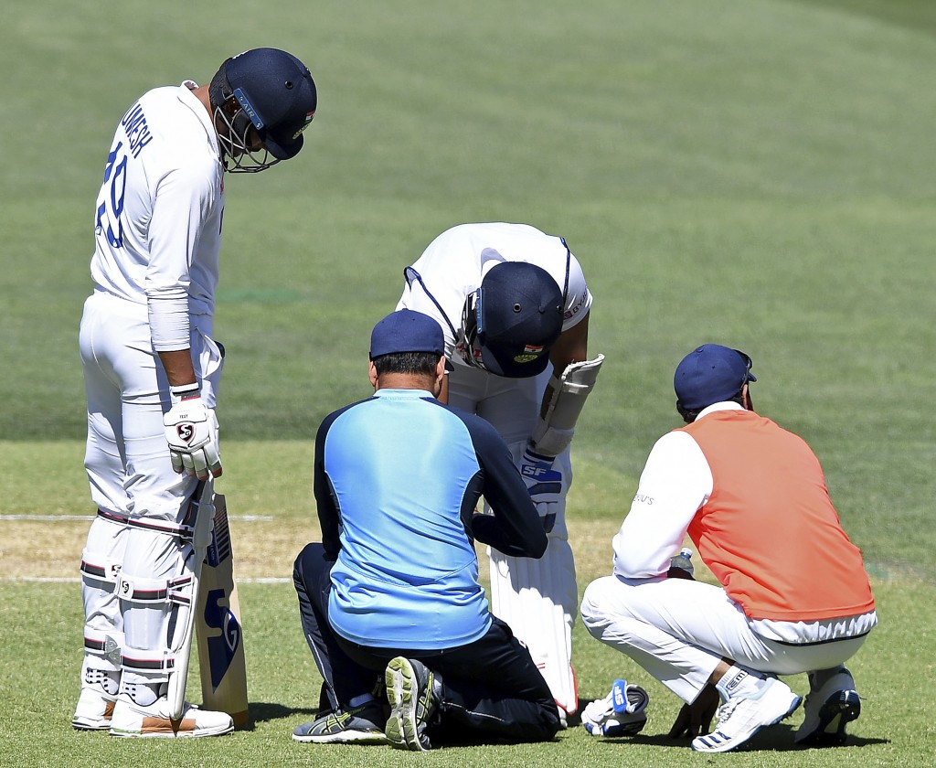 India's Mohammed Shami, second right, is attended to by medical staff after he was struck on the forearm on the third day of their cricket test match ...