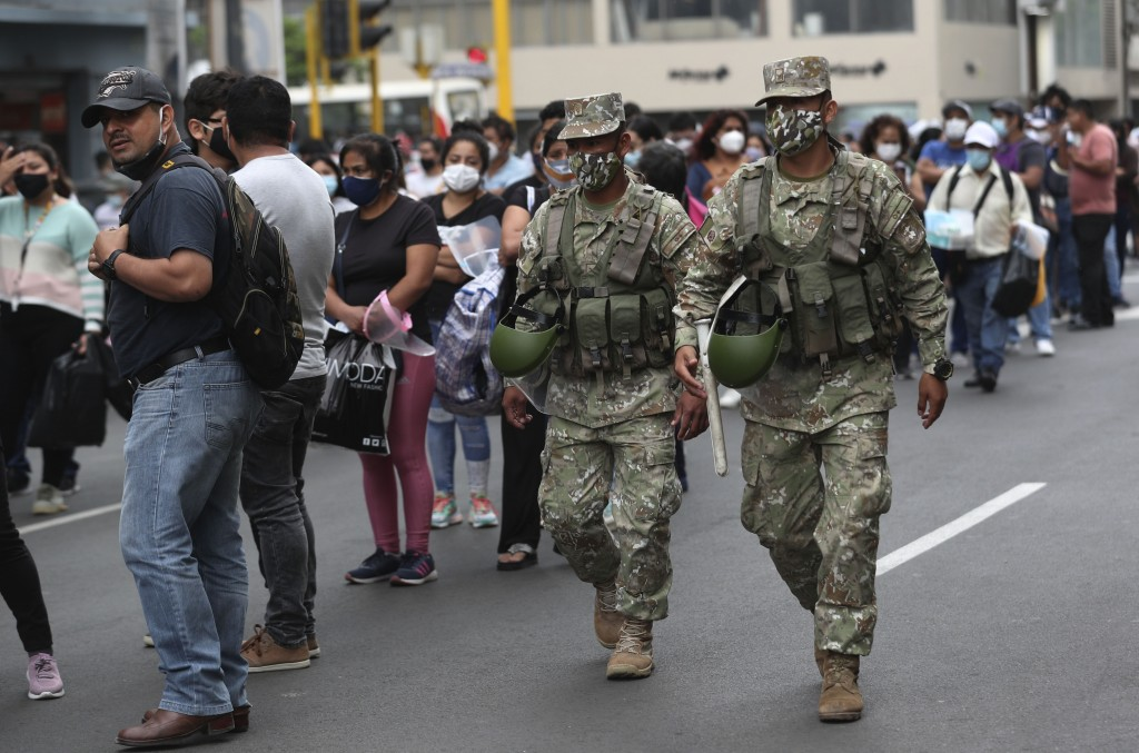 Soldiers wearing face masks amid the spread of coronavirus walk amid shoppers at Mesa Redonda Market, a popular dpot for Christmas shopping in Lima, P...