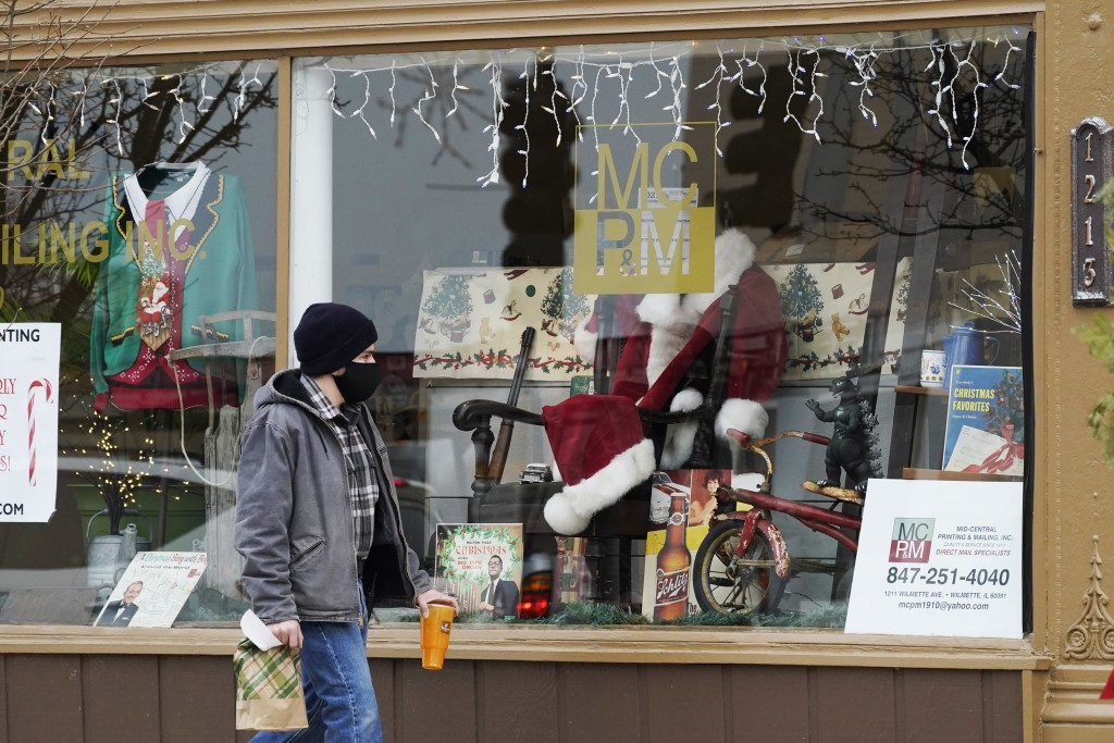 Christmas cards and costumes are displayed in the window at Mid Central Printing & Mailing store in Wilmette, Ill., Friday, Dec. 18, 2020. Isolated by...