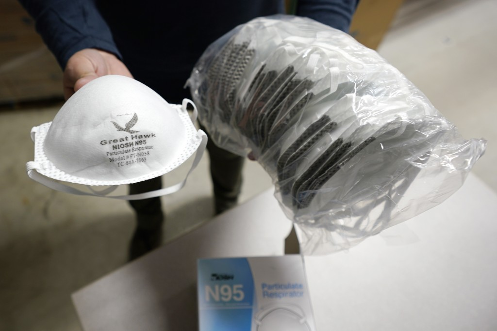 Ray Bellia holds up N95 personal protective masks, used by medical and law enforcement professionals, in the warehouse of his Body Armor Outlet store,...