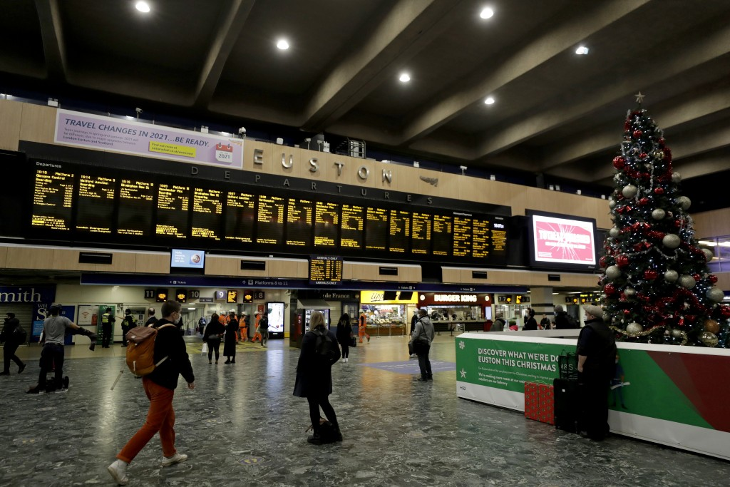 People wait to board trains with destinations including the Midlands, north of England and Scotland at Euston railway station in London, Friday, Dec. ...