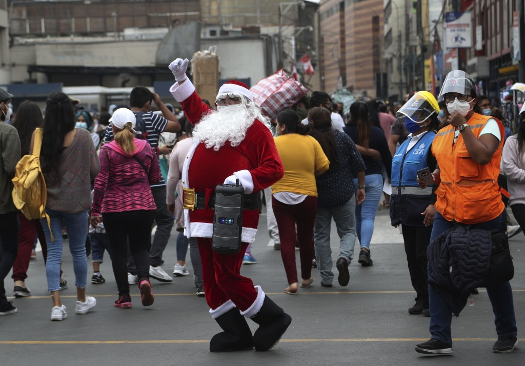 A man dressed as Santa Claus waves amid pedestrians at the Mesa Redonda Market, a popular spot for Christmas shopping, amid the COVID-19 pandemic in L...