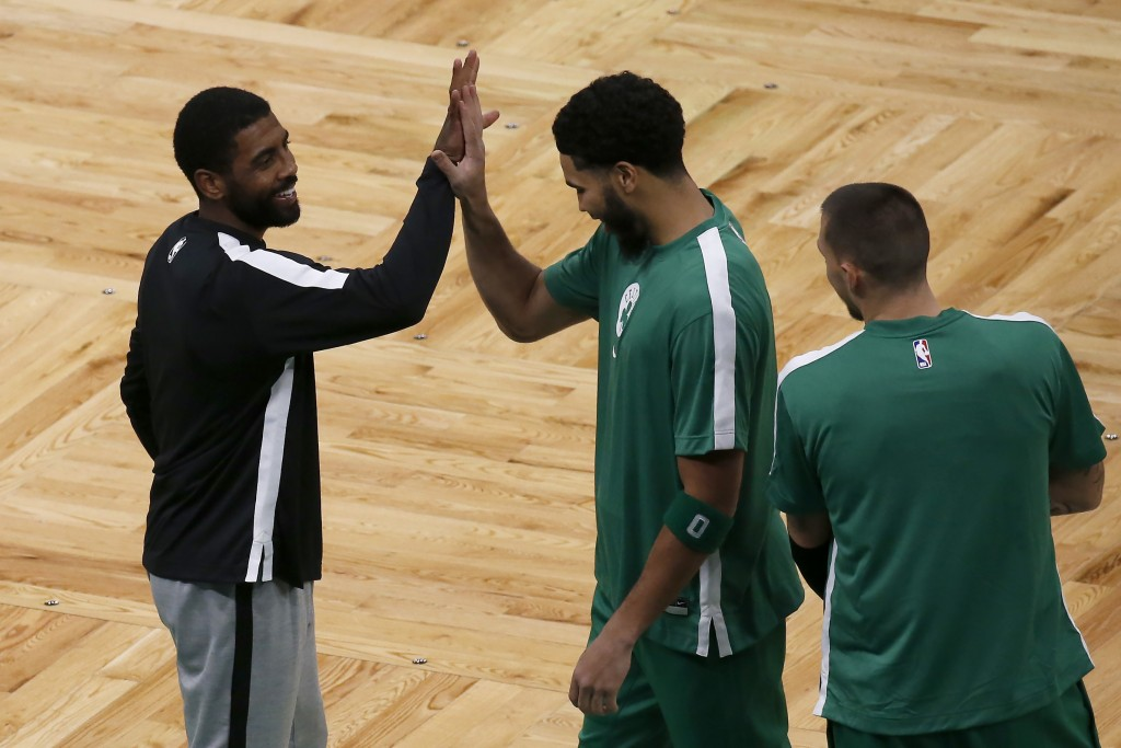 Brooklyn Nets guard Kyrie Irving, left, smiles as he greets former teammate Boston Celtics forward Jayson Tatum (0) as Celtics' Daniel Theis, right, l...