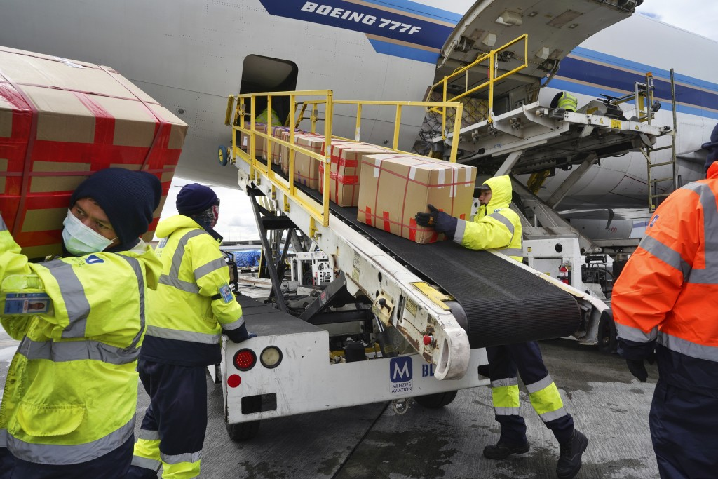 Wearing protective masks, ground crew at the Los Angeles International airport unload supplies of medical personal protective equipment from a China S...