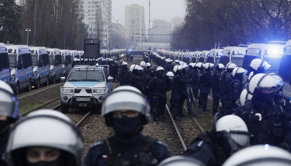 Police in riot gear block the path of anti-government protesters trying to reach the home of the ruling party leader, Jaroslaw Kaczynski, in Warsaw, P...