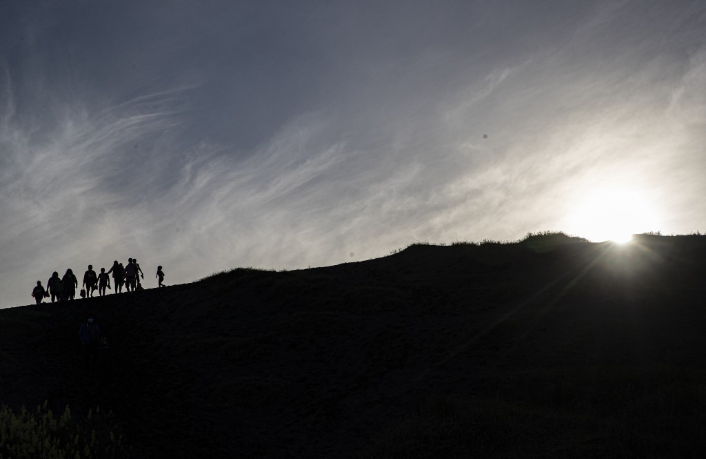 People walk on a dune, a day before a total eclipse in Nahuelpan, La Araucania, Chile, Sunday, Dec. 13, 2020. The total eclipse will be visible from C...