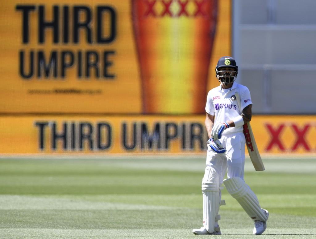 India's Virat Kohli, waits as he walks off as the third umpire checks the catch that takes Kohli's wicket for 4 runs against Australia on the third da...