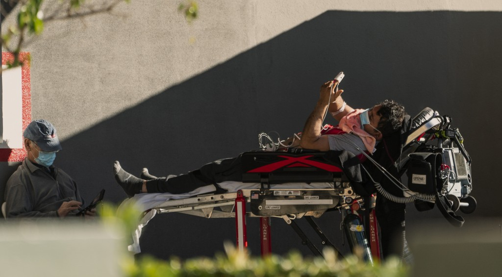 An unidentified patient uses his mobile phone while receiving oxygen on a stretcher, as Los Angeles Fire Department Paramedics monitor him outside the...
