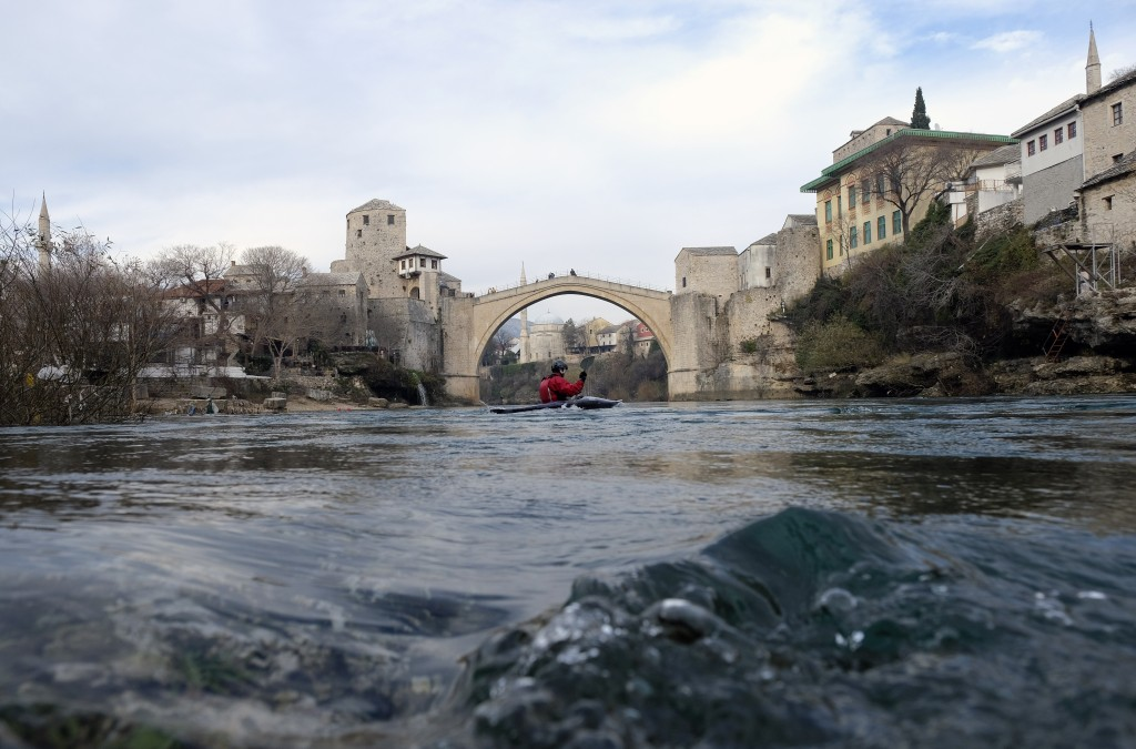 A man paddles his kayak on the Neretva river in front of the Old Bridge, one of Bosnia's best known landmarks in Mostar, Bosnia, Friday, Dec. 18, 2020...