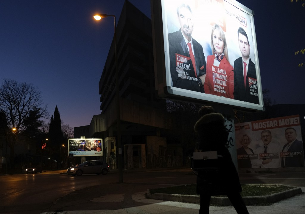 A woman passes by pre-elections billboards in Mostar, Bosnia, Friday, Dec. 18, 2020. Bosnia's ethnically divided southern city of Mostar is holding it...