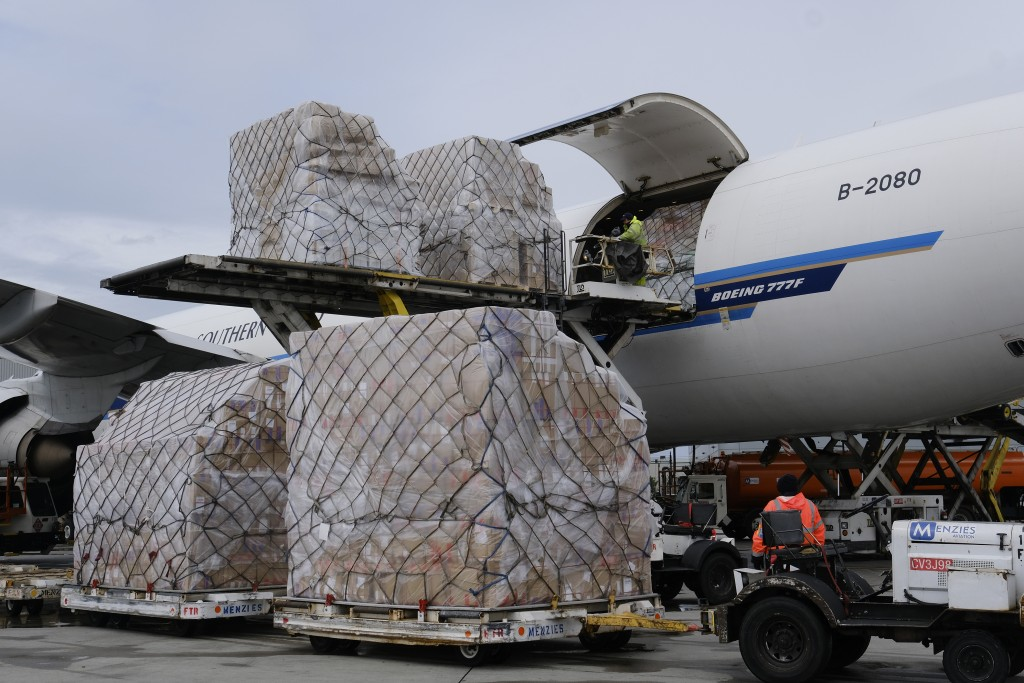 FILE - In this April 10, 2020, file photo, a ground crew at Los Angeles International Airport unload pallets of medical personal protective equipment ...