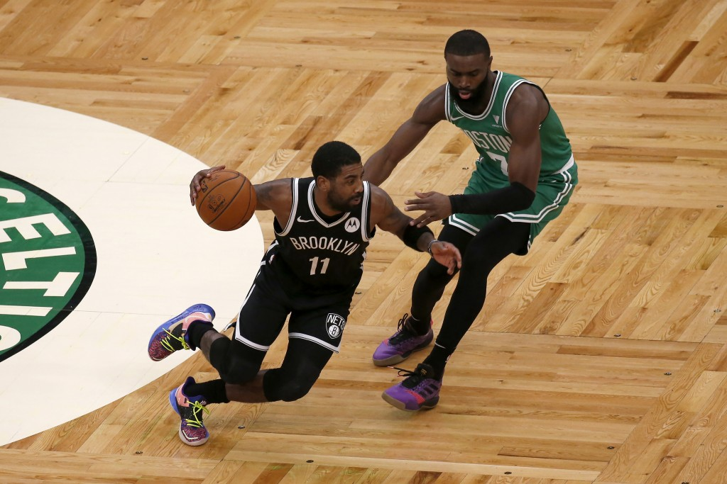 Brooklyn Nets guard Kyrie Irving (11) drives against Boston Celtics guard Jaylen Brown (7) during the first half of an NBA preseason basketball game, ...