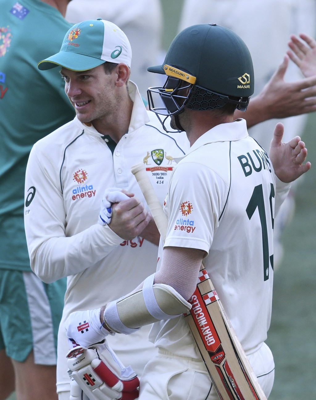 Australia's Joe Burns, right, is congratulated by his captain Tim Paine after Burns hit a 6 to win their match over India on the third day of their cr...