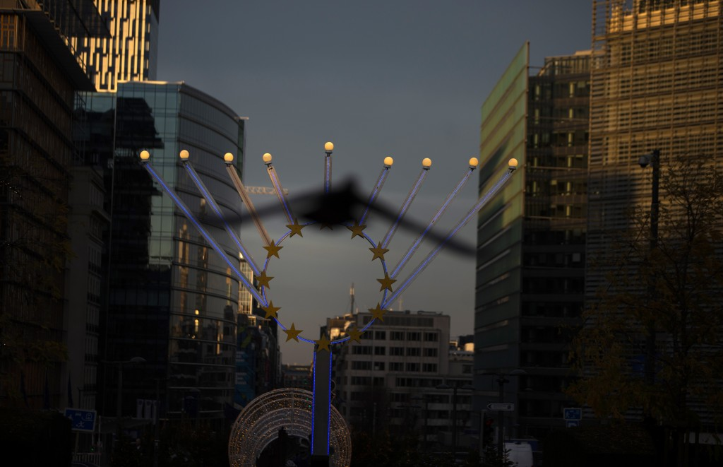 A bird flies in front of a menorah outside EU headquarters in Brussels, Saturday, Dec. 19, 2020. The European Union and the United Kingdom were starti...