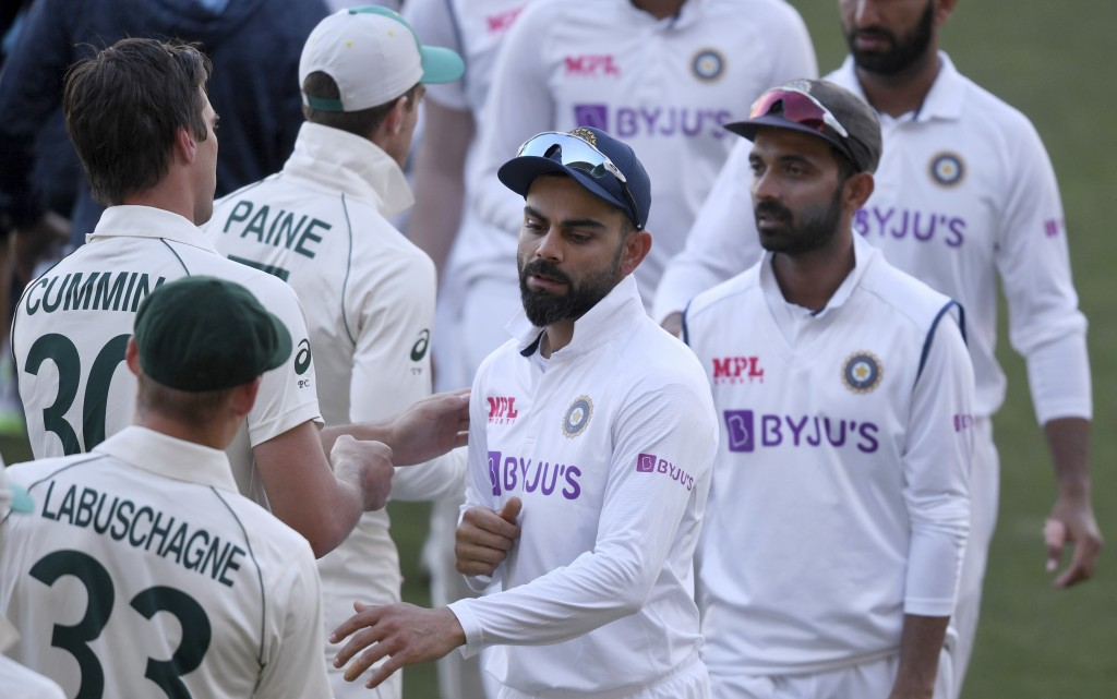 India's Virat Kohli, center, shakes hands with Australian players on the third day of their cricket test match at the Adelaide Oval in Adelaide, Austr...
