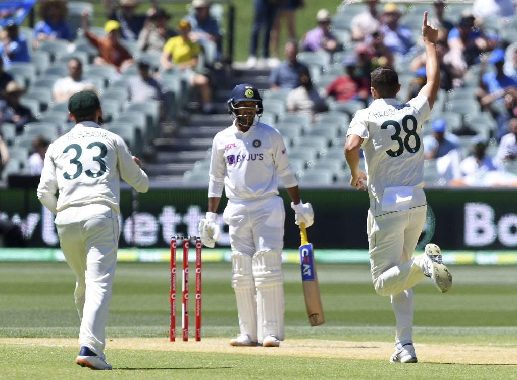 Australia's Josh Hazlewood, right, celebrates taking the wicket of India's Mayank Agarwal, center, on the third day of their cricket test match at the...