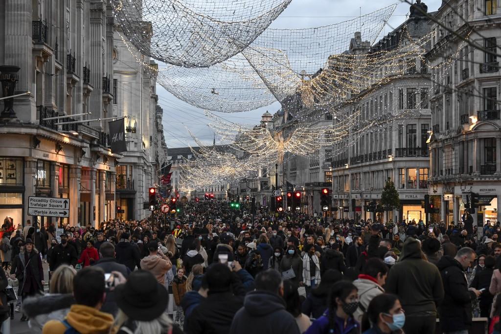 Crowds of shoppers walk under the Christmas lights in Regent Street, in London, Saturday, Dec. 12, 2020. Health Secretary Matt Hancock says infections...
