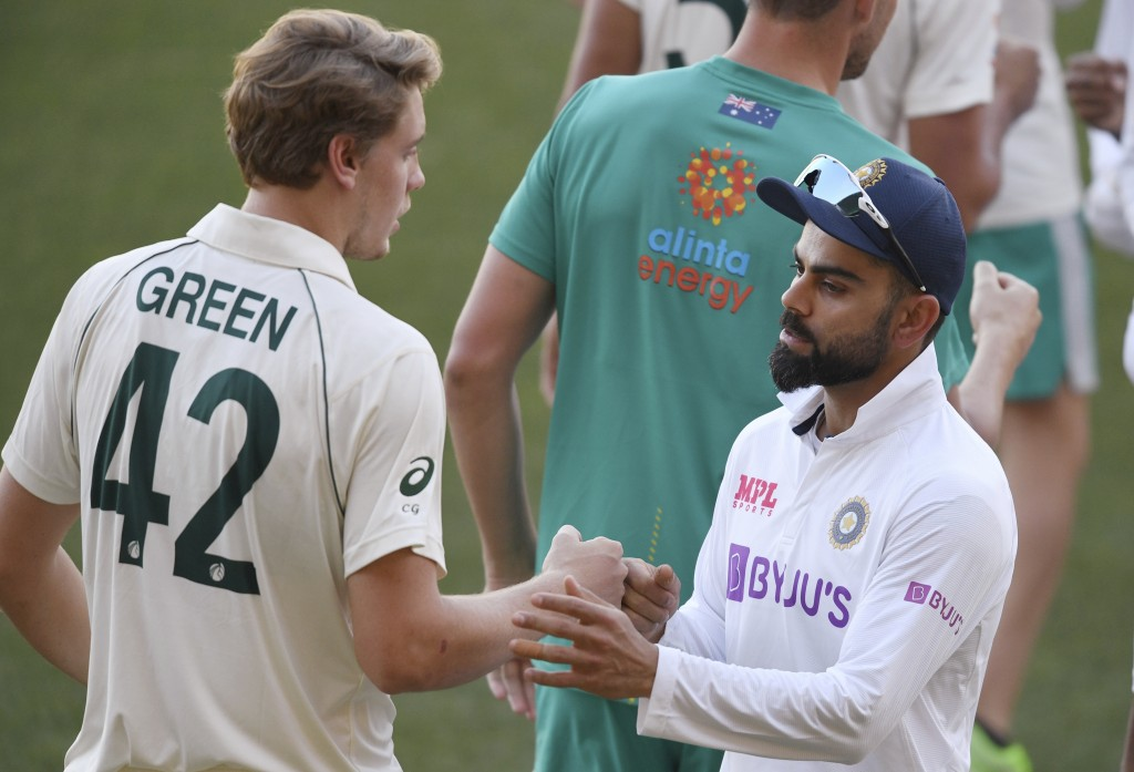 India's Virat Kohli, right, shakes hands with Australia's Cameron Green after Australia won on the third day of their cricket test match at the Adelai...