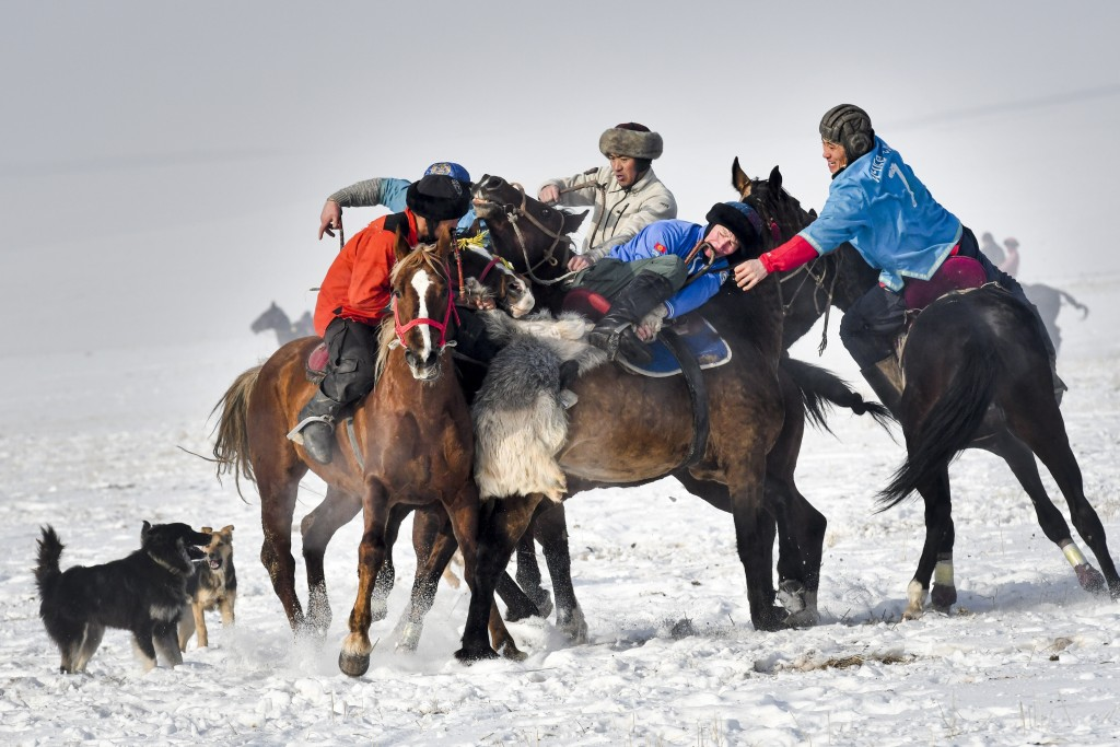 Riders compete during a kok boru, also called ulak tartysh, a traditional game in which players on horseback maneuver with a goat's carcass and score ...