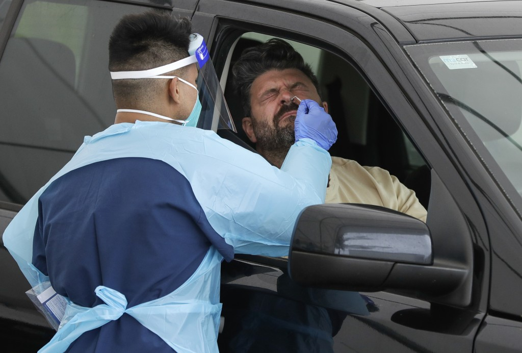 A man receives a COVID-19 test at a drive through testing station at a beach in Sydney, Australia, Saturday, Dec. 19, 2020. Sydney's northern beaches ...
