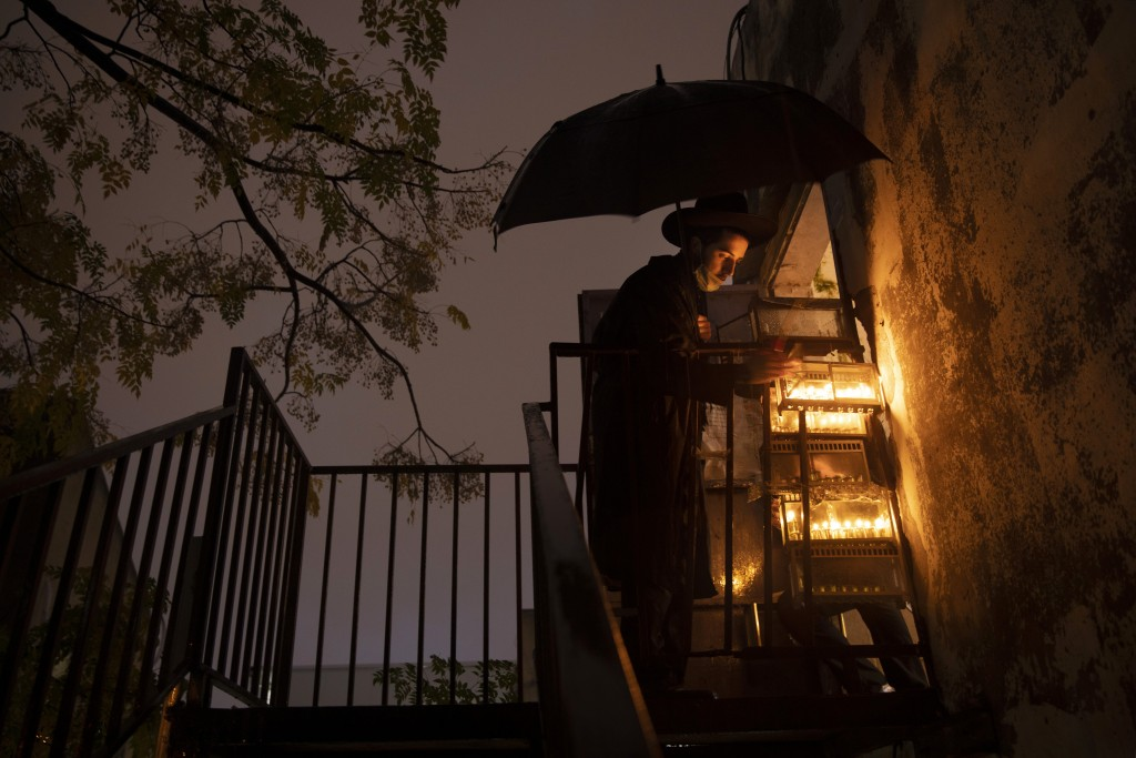 An ultra-Orthodox Jewish yeshiva student lights candles under an umbrella in the rain during the Jewish holiday of Hanukkah in the ultra-Orthodox city...