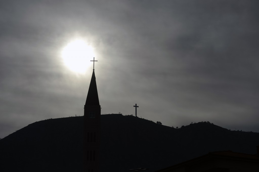 The tower of Catholic church rises into the sky in Mostar, Bosnia, Friday, Dec. 18, 2020. Bosnia's ethnically divided southern city of Mostar is holdi...