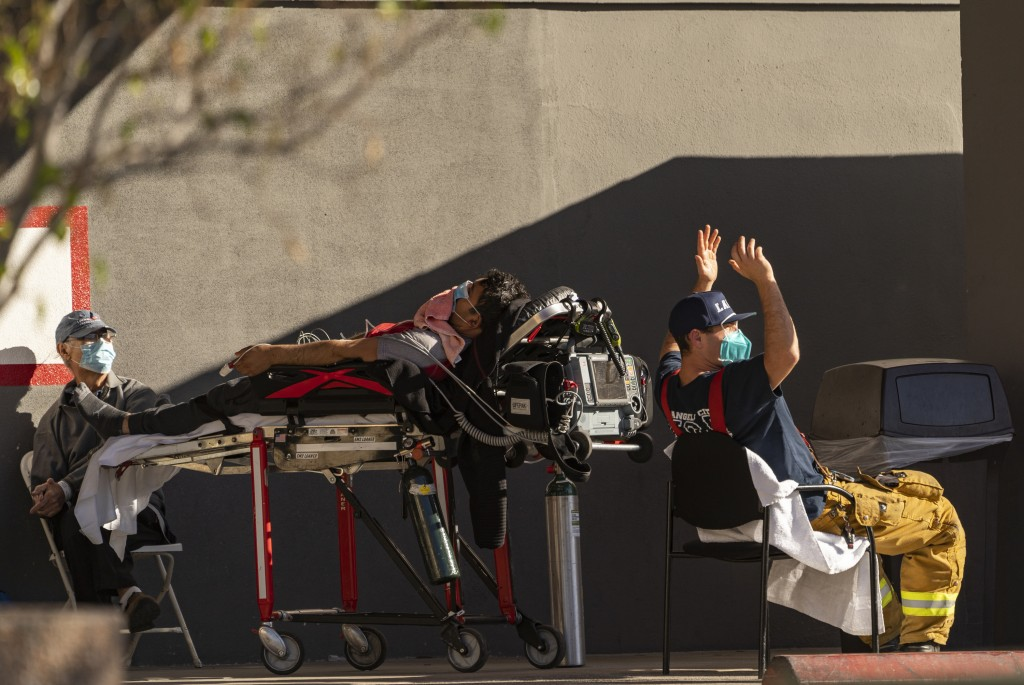 An unidentified patient receives oxygen on a stretcher, while Los Angeles Fire Department Paramedics monitor him outside the Emergency entrance, waiti...
