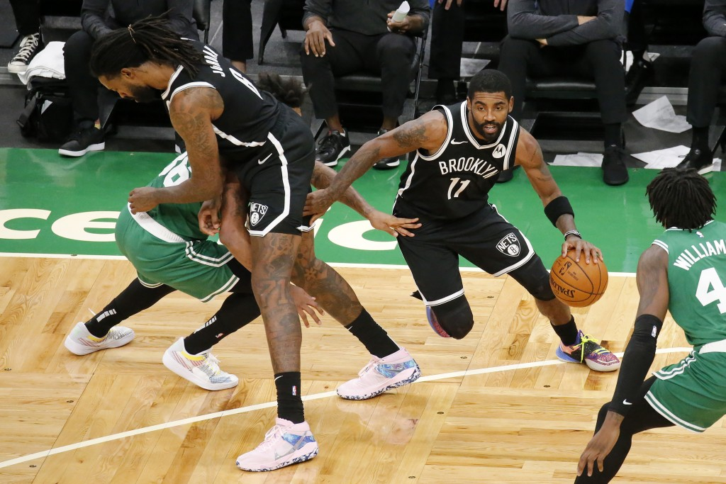 Brooklyn Nets guard Kyrie Irving (11) drives past Boston Celtics guard Marcus Smart as teammate DeAndre Jordan sets a pick during the first half of an...