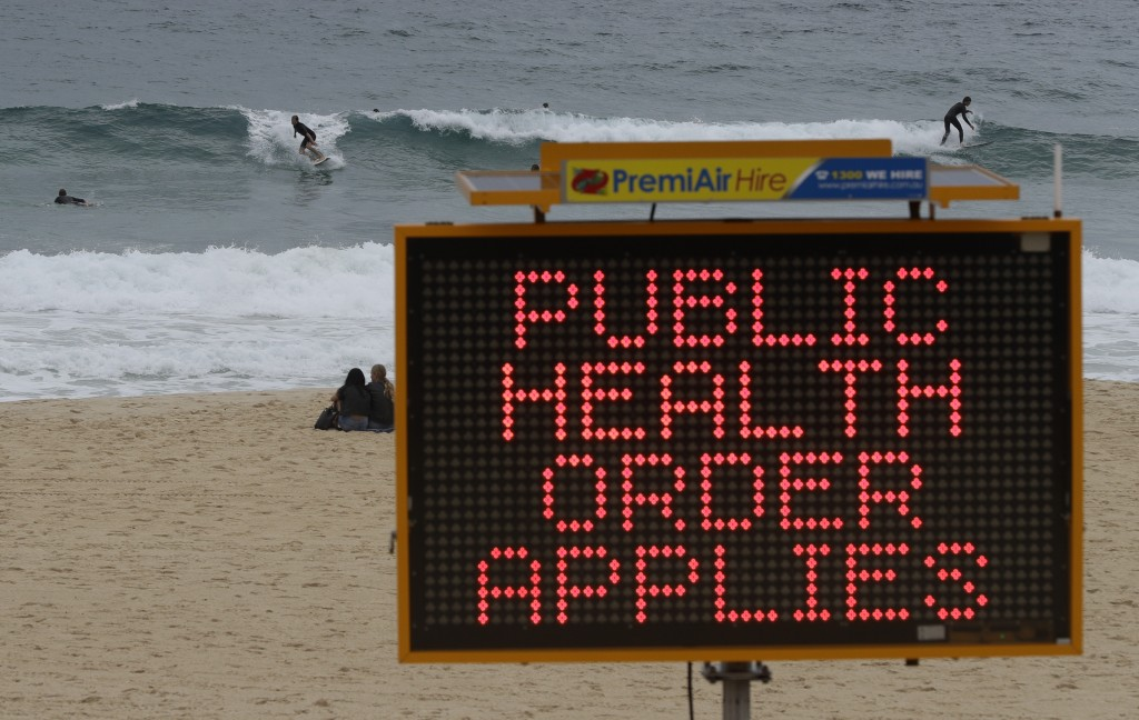 Surfers ride a wave past a sign at a beach in Sydney, Australia, Saturday, Dec. 19, 2020. Sydney's northern beaches will enter a lockdown similar to t...