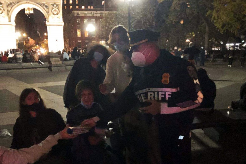 This photo provided by the New York City Sheriff, shows a Deputy Sheriff distributing medical face masks in New York's Washington Square Park, Oct. 21...