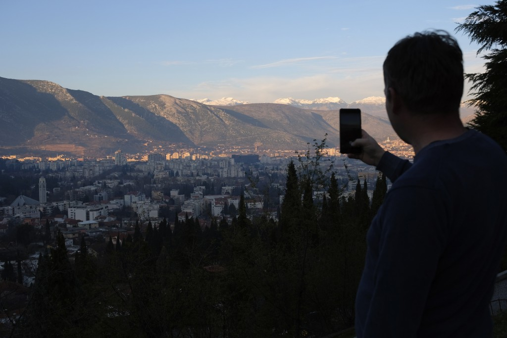 A man with his phone takes a panoramic photo of Mostar, Bosnia, Friday, Dec. 18, 2020. Bosnia's ethnically divided southern city of Mostar is holding ...