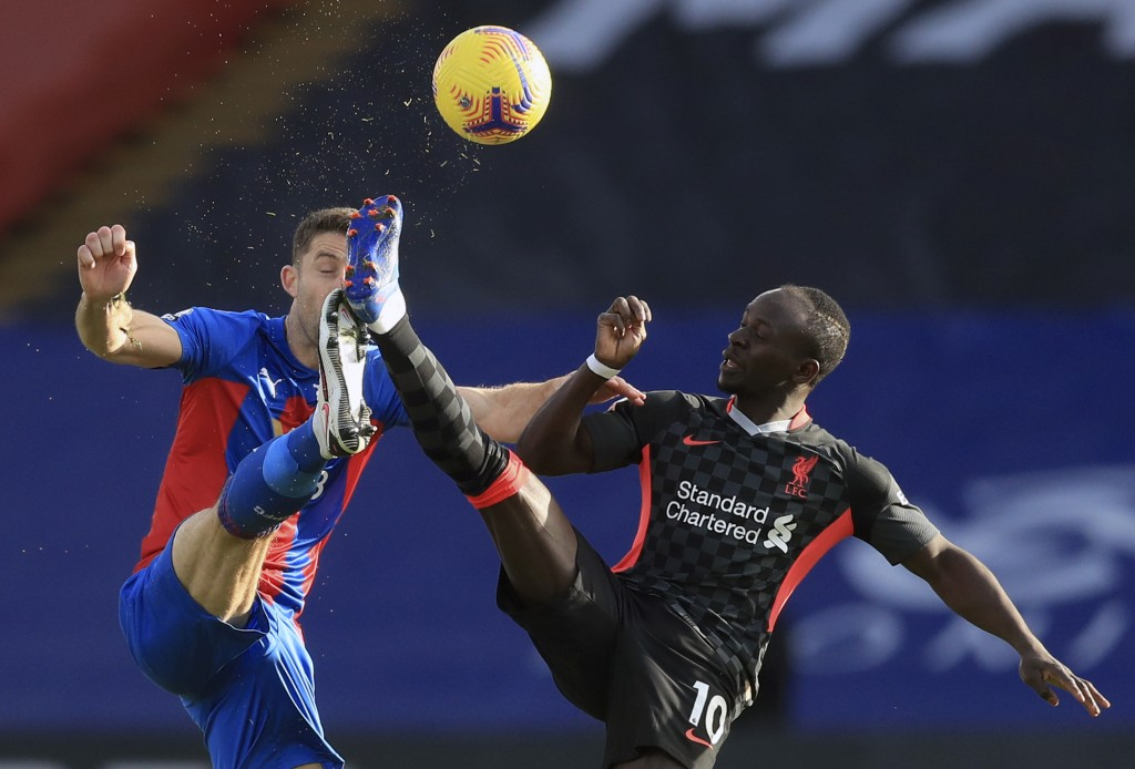Crystal Palace's Gary Cahill, left, duels for the ball with Liverpool's Sadio Mane during the English Premier League soccer match between Crystal Pala...
