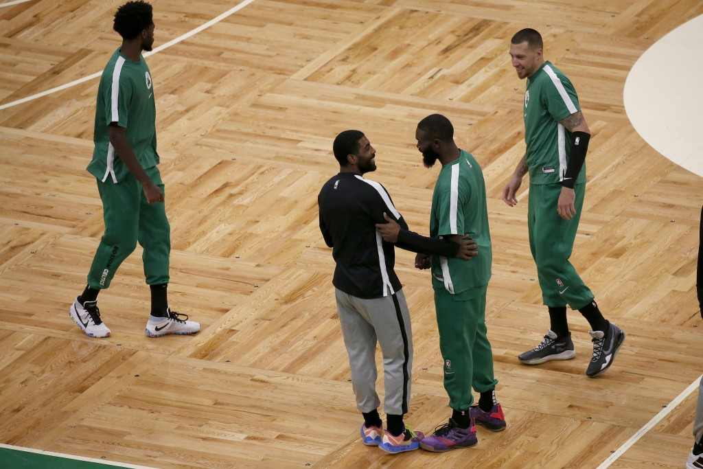 Brooklyn Nets guard Kyrie Irving, center, greets former teammate Boston Celtics guard Jaylen Brown as Celtics' Daniel Theis, right, looks on before an...