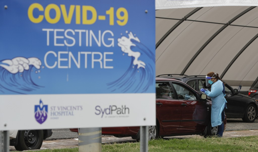 People wait at a drive through COVID-19 testing station at a beach in Sydney, Australia, Saturday, Dec. 19, 2020. Sydney's northern beaches will enter...