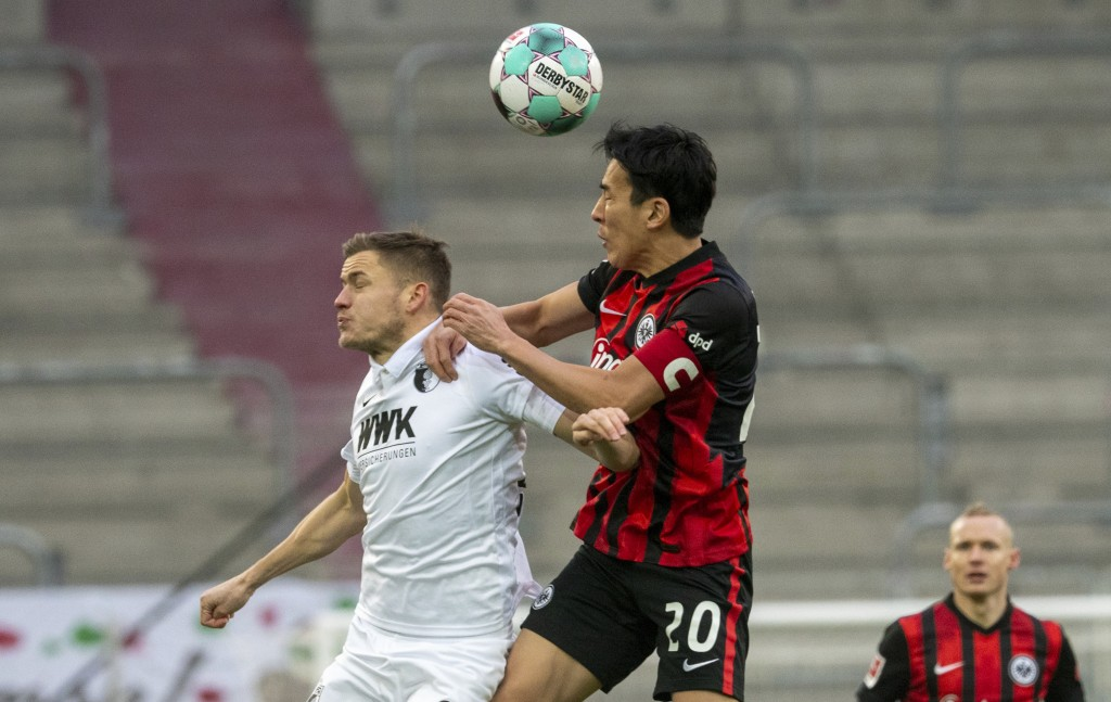 Augsburg's Alfred Finnbogason, left, and Frankfurt's Makoto Hasebe challenge for the ball during the Bundesliga soccer match between FC Augsburg and E...
