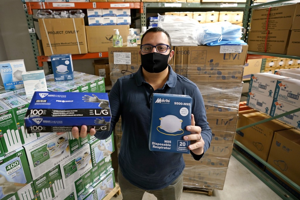 Ray Bellia holds up personal protective masks and gloves, used by medical and law enforcement professionals, in the warehouse of his Body Armor Outlet...