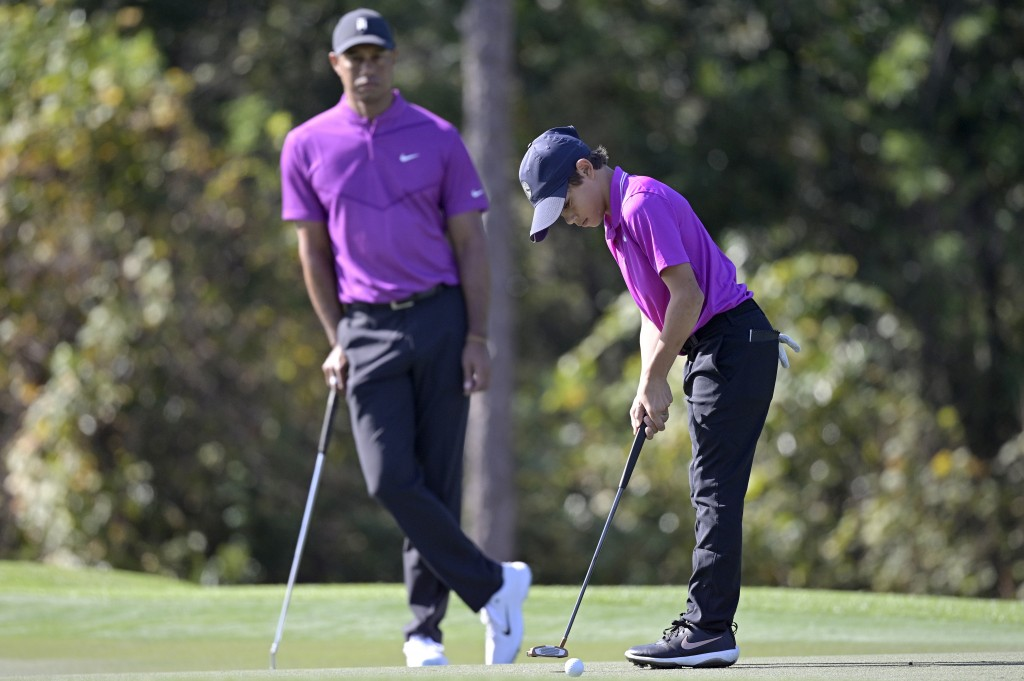 Tiger Woods watches as his son Charlie sinks a putt on the first green during the first round of the PNC Championship golf tournament, Saturday, Dec. ...