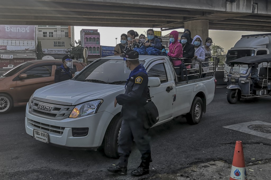 A group of migrant workers arrive in a back of a truck to get screened for COVID-19 in Samut Sakhon, South of Bangkok, Thailand, Sunday, Dec. 20, 2020...